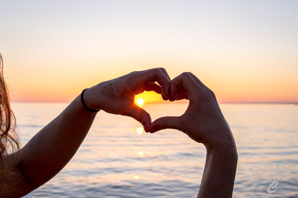 main en forme de coeur couché de soleil avec soleil dans la main